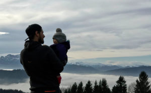 Dad holding baby overlooking mountains