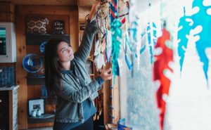 Justine hangs new glass artwork in window